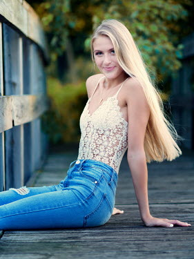 Elisabeth Ansley BLONDE GIRL IN JEANS SITTING ON WOODEN BRIDGE Women