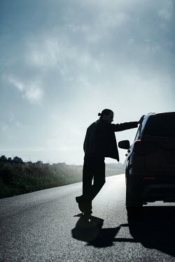 Magdalena Russocka silhouette of modern man standing next to car on countryside
