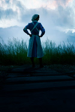 Stephen Mulcahey NURSE STANDING ON COUNTRY PATH IN SHADOW Women