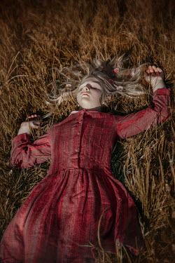 Natasza Fiedotjew Girl in vintage dress lying in grass in sunset