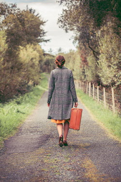 Marie Carr WOMAN CARRYING SUITCASE WALKING IN COUNTRY ROAD Women