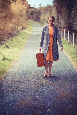 Marie Carr WOMAN CARRYING SUITCASE IN COUNTRY ROAD Women