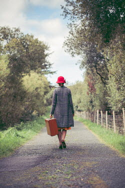 Marie Carr WOMAN IN COAT CARRYING SUITCASE IN COUNTRYSIDE Women