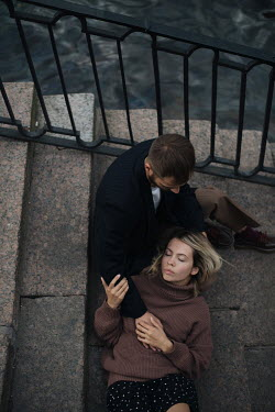 Alina Zhidovinova AFFECTIONATE YOUNG COUPLE ON STEPS BY RIVER Couples