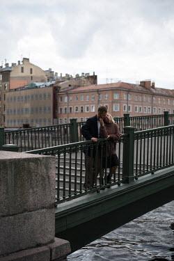Alina Zhidovinova HUGGING COUPLE ON URBAN BRIDGE WITH RIVER Couples