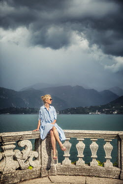 Evelina Kremsdorf BLONDE WOMAN ON BALCONY BY STORMY LAKE Women