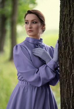 Jaroslaw Blaminsky BRUNETTE WOMAN IN PURPLE STANDING BY TREE Women