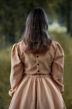 Jaroslaw Blaminsky WOMAN WITH DARK HAIR IN DRESS STANDING IN COUNTRYSIDE Women
