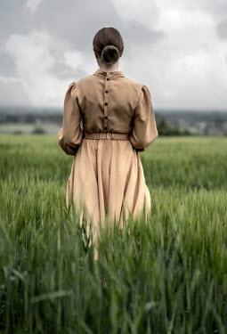 Jaroslaw Blaminsky BRUNETTE WOMAN IN DRESS STANDING IN FIELD Women