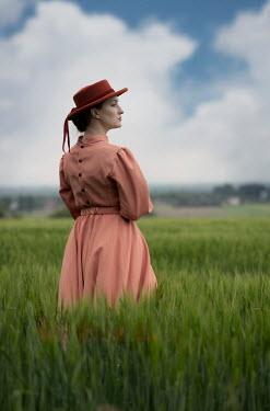 Jaroslaw Blaminsky WOMAN IN HAT STANDING IN FIELD Women