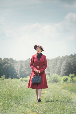 Joanna Czogala RETRO WOMAN IN HAT WALKING IN COUNTRYSIDE Women