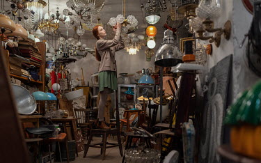 Maxim Guselnikov WOMAN ON CHAIR WITH CEILING LIGHTS IN JUNK SHOP Women
