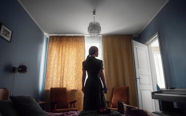 Maxim Guselnikov WOMAN STANDING IN BEDROOM WITH CLOSED CURTAINS Women