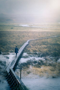 Natasza Fiedotjew Man walking on long wooden footbridge over lake