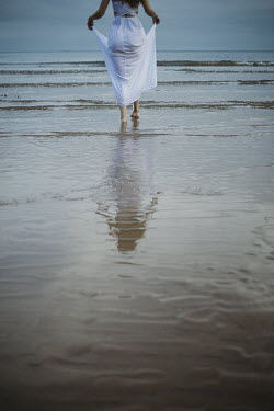 Shelley Richmond WOMAN IN WHITE DRESS PADDLING IN SEA Women
