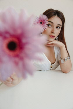 Greta Larosa BRUNETTE WOMAN SITTING HOLDING PINK FLOWER Women