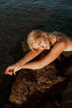 Greta Larosa BLONDE WOMAN IN SEA LYING ON ROCK Women