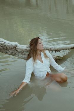 Greta Larosa SERIOUS WOMAN LEANING ON BRANCH IN WATER Women