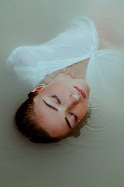 Greta Larosa WOMAN IN WHITE SHIRT FLOATING IN WATER Women