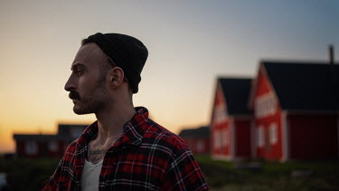 Maxim Guselnikov MAN IN PLAID SHIRT BY HOUSES AT SUNSET Men