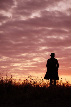 Tim Robinson SILHOUETTED MAN IN HAT STANDING IN FIELD Men