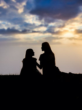 Elisabeth Ansley SILHOUETTED MOTHER AND DAUGHTER SITTING IN FIELD AT SUNSET Children