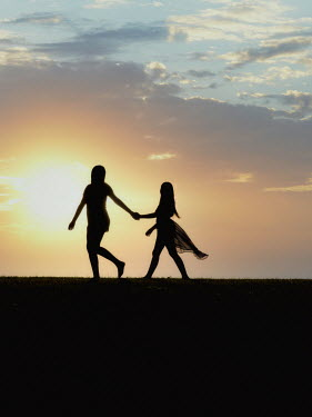 Elisabeth Ansley SILHOUETTED MOTHER AND DAUGHTER HOLDING HANDS OUTDOORS Children