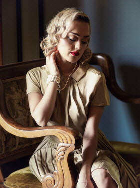 Elisabeth Ansley BLONDE WOMAN IN DRESS WITH PEARLS SITTING INDOORS Women
