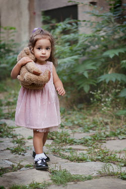 Kerstin Marinov LITTLE GIRL HOLDING TEDDY ON COBBLED ROAD Children