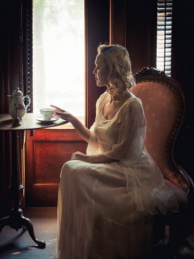Elisabeth Ansley BLONDE WOMAN SITTING BY WINDOW DRINKING COFFEE Women