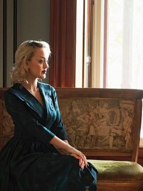 Elisabeth Ansley BLONDE WOMAN IN BLUE DRESS SITTING INDOORS Women