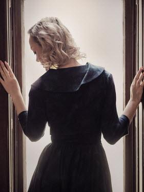 Elisabeth Ansley BLONDE WOMAN STANDING BY WINDOW INDOORS Women
