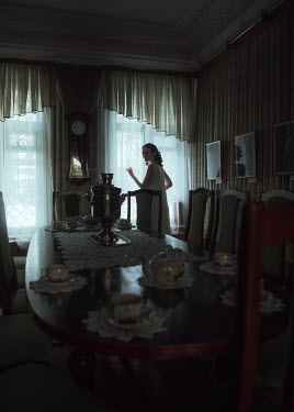 Ekaterina Pavlova WOMAN BY WINDOW IN DINING ROOM OF HOUSE Women