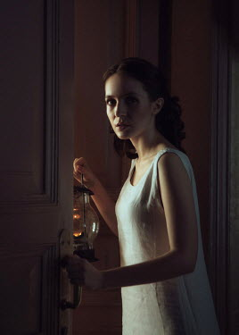 Ekaterina Pavlova BRUNETTE WOMAN OPENING DOOR HOLDING LAMP Women