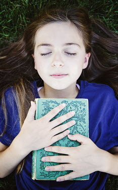 Isabelle Lafrance LITTLE GIRL LYING ON GRASS HOLDING BOOK Children
