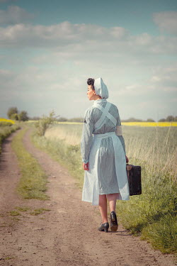 Joanna Czogala RETRO NURSE CARRYING SUITCASE ON COUNTRY ROAD Women