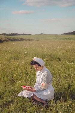 Joanna Czogala WARTIME NURSE SITTING HOLDING LETTERS IN COUNTRYSIDE Women