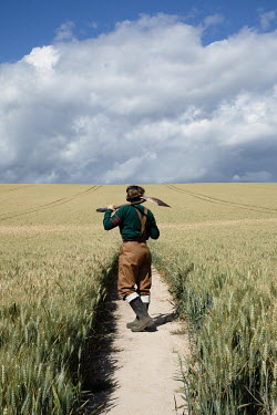 Matilda Delves WOMAN IN DUNGAREES WITH SHOVEL IN FARMLAND Women