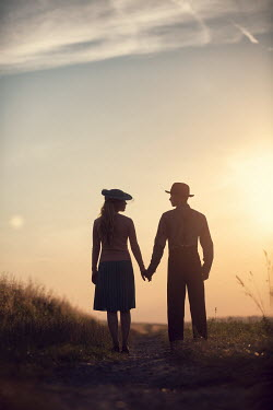 Magdalena Russocka young retro couple standing in field at sunset