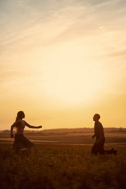Magdalena Russocka young couple running towards each other in field at sunset