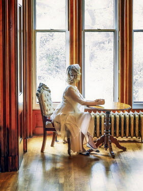 Elisabeth Ansley BLONDE WOMAN SITTING BY WINDOW IN LARGE HOUSE Women