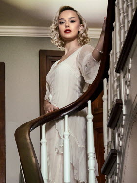 Elisabeth Ansley BLONDE WOMAN IN WHITE STANDING ON STAIRCASE Women