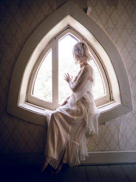 Elisabeth Ansley BLONDE WOMAN IN WHITE SITTING IN ATTIC WINDOW Women