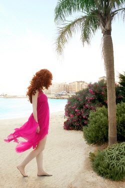ILINA SIMEONOVA WOMAN WITH RED HAIR ON BEACH BY PALM TREE Women