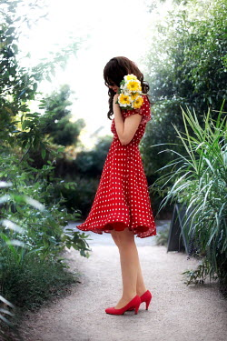 ILINA SIMEONOVA WOMAN IN RED DRESS ON PATH CARRYING FLOWERS Women