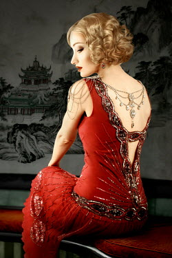 ILINA SIMEONOVA BLONDE WOMAN SITTING IN RED BEADED DRESS Women