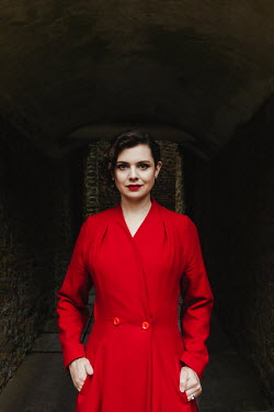 Matilda Delves WOMAN IN RED COAT STANDING IN TUNNEL Women