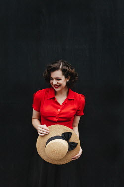 Matilda Delves SMILING BRUNETTE WOMAN IN RED BLOUSE HOLDING HAT Women