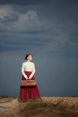 Magdalena Russocka historical woman with  bag standing in field