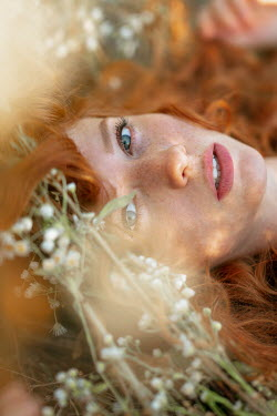Nina Masic WOMAN WITH RED HAIR LYING IN FLOWERS OUTDOORS Women